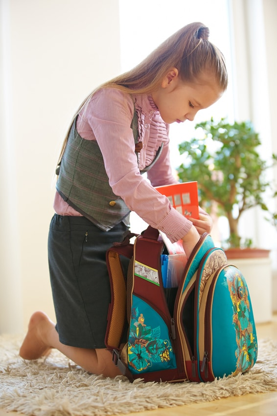 Kind packt zu Hause den Schulranzen für die Schule