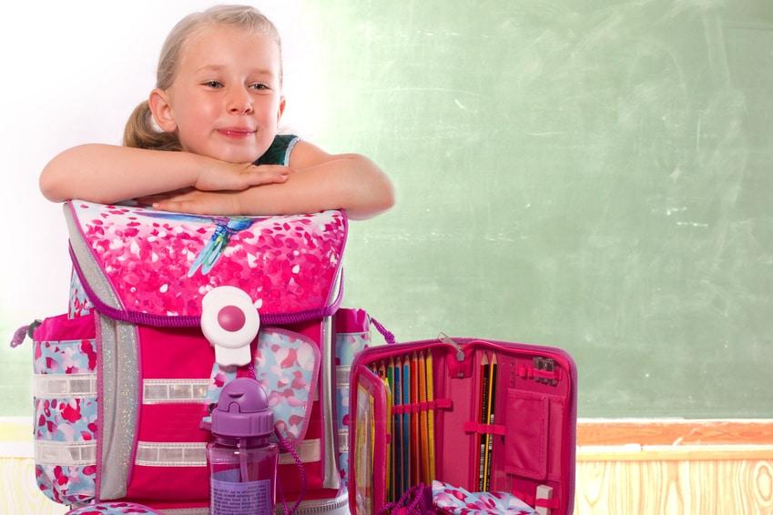 stolzes Mädchen zeigt im Klassenzimmer ihre Schulsachen