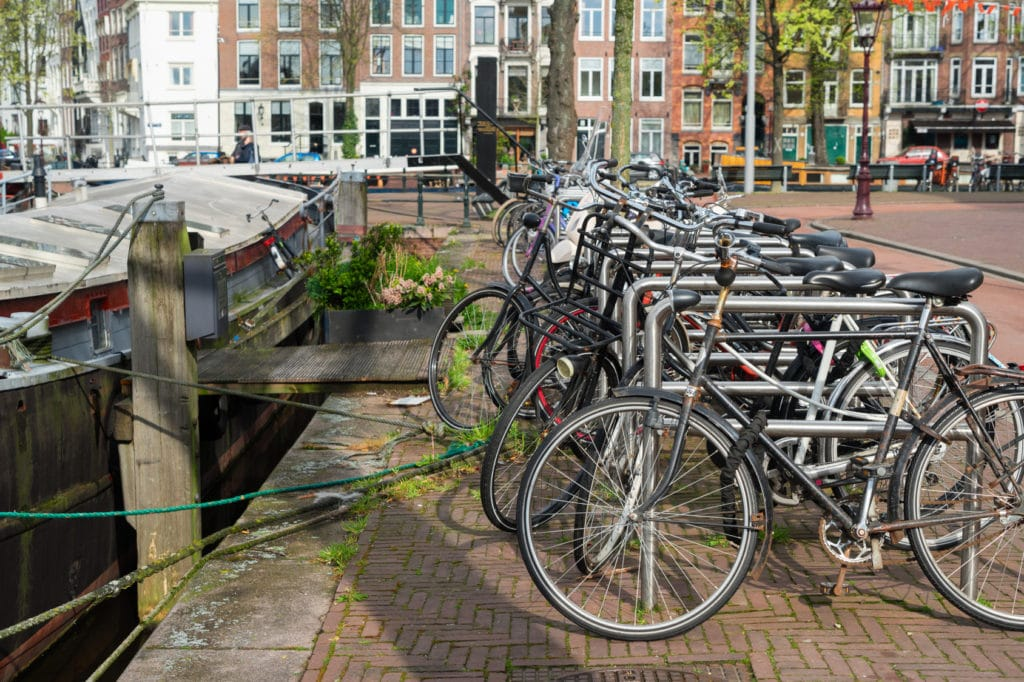 Row of bicycles standing next to canal in Amsterdam, Netherlands