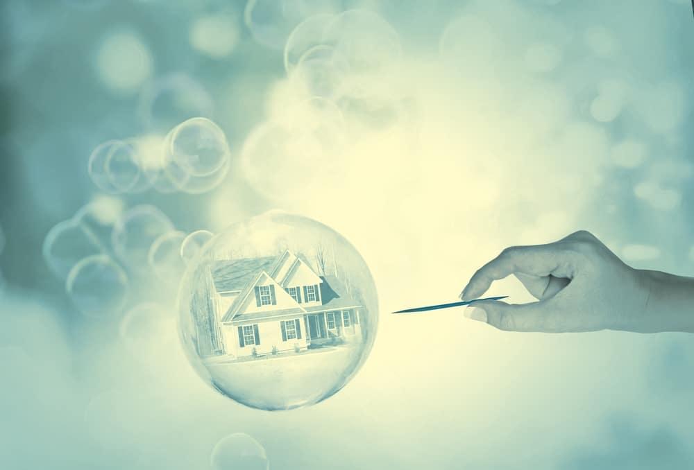 Blase mit Haus kurz vor dem Platzen